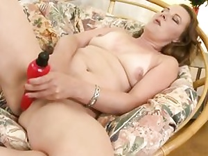 Steaming mother is feeding her moist pussy crevasse with a huge crimson dildo on couch